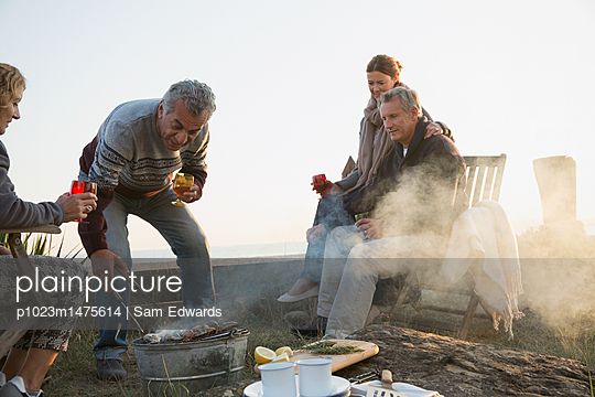 Mature couples barbecuing and drinking wine on sunset beach - p1023m1475614 by Sam Edwards