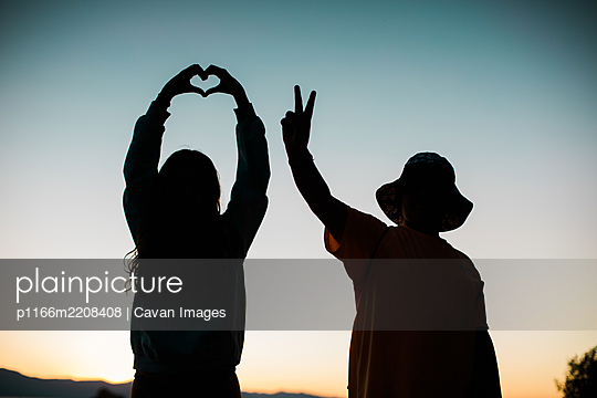 Love and Peace Sign Silhouettes with Colorful Sky - Young People - p1166m2208408 by Cavan Images