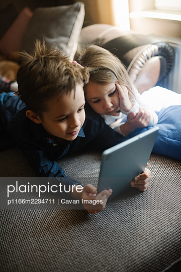 Siblings lying on sofa at home and playing with tablet together. - p1166m2294711 by Cavan Images