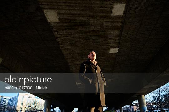 Mann im Mantel steht unter einer Brücke - p890m1217300 von Mielek