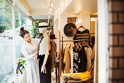 Woman working in a fashion boutique in Tokyo, Japan, dressing a mannequin. - p1100m1185821 by Mint Images