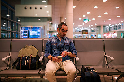Man checking time while sitting on chair in airport departure area - p1166m2035327 by Cavan Social