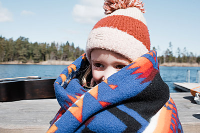young girl wrapped up in a blanket by the lake keeping warm - p1166m2189855 by Cavan Images