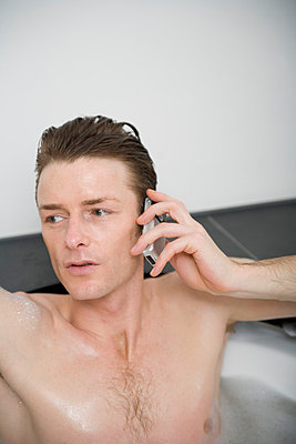 Man sitting in a bathtub and holding a mobile phone - p3013848f by Stella