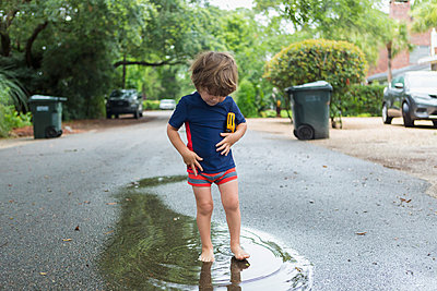Caucasian boy standing in puddle on street - p555m1522938 by Marc Romanelli