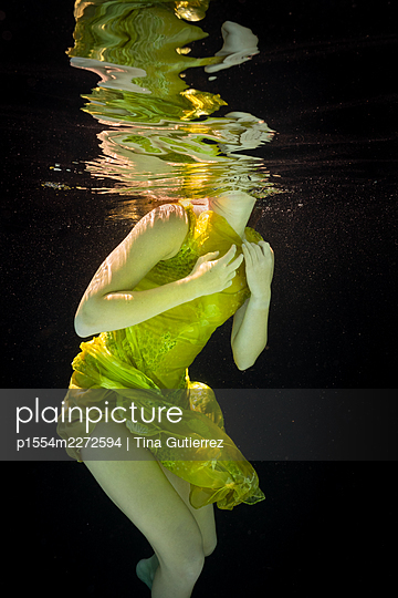 Woman in yellow dress under water - p1554m2272594 by Tina Gutierrez