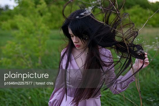 Woman in purple dress on a meadow - p1646m2257577 by Slava Chistyakov