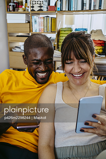 Cheerful couple sharing mobile phone sitting together in living room at home - p426m2298244 by Maskot