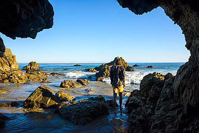 Rear view of man standing at shore against clear sky seen through cave - p1166m1423334 by Cavan Images