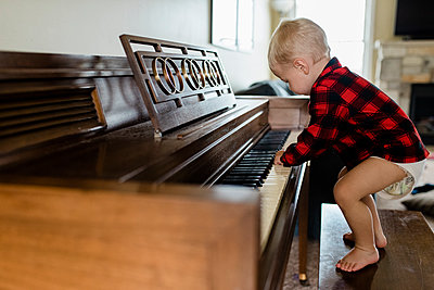 Baby boy in diaper stands on bench playing piano at home - p1166m2136277 by Cavan Images