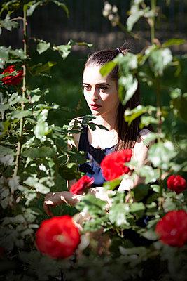 Woman behind a rose bush, portrait - p1248m2187195 by miguel sobreira