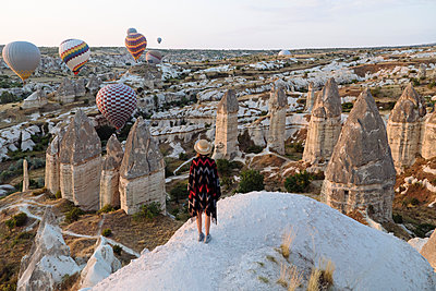 Young woman and hot air balloons in the evening, Goreme, Cappadocia, Turkey - p300m2132132 by Konstantin Trubavin