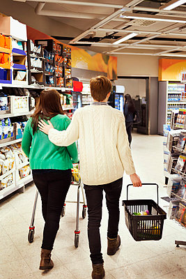 Rear view of couple walking in supermarket - p426m1017977f by Maskot