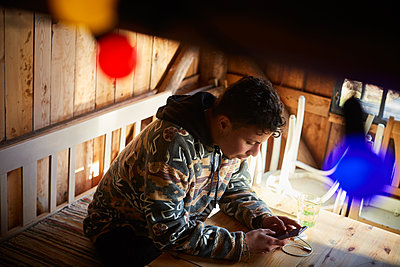 High angle view of young man using smart phone while sitting in cottage - p426m2117217 by Maskot