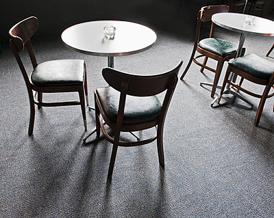 Tables and chairs in empty cafe - p555m1453048 by Spaces Images