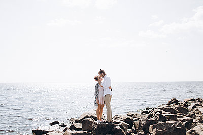 Middle Eastern couple hugging on rocks near ocean - p555m1481912 by Aleksandr Kuzmin