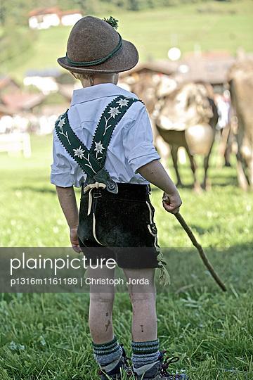 Junge in Tracht auf einer Wiese beim Viehscheid, Allgäu, Bayern, Deutschland - p1316m1161199 von Christoph Jorda