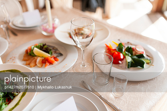 Drinking glasses and food on dining table during wedding - p1427m2077610 by Mykhailo Lukashuk