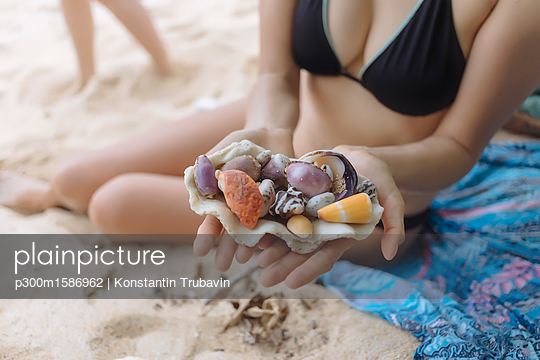 Young woman at the beach holding seashells - p300m1586962 von Konstantin Trubavin