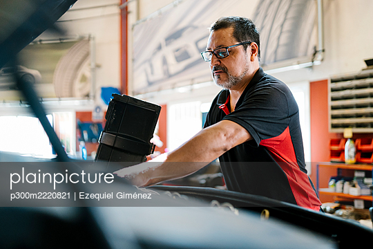 Male mechanic repairing car while standing in garage - p300m2220821 by Ezequiel Giménez