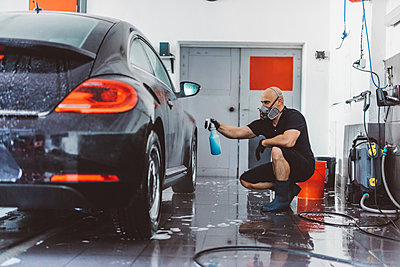 Male worker spraying water on car while crouching in workshop - p1166m2060373 by Cavan Images