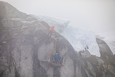 Climbers rappelling onto portaledge as stormy weather blows in. - p1166m2212665 by Cavan Images