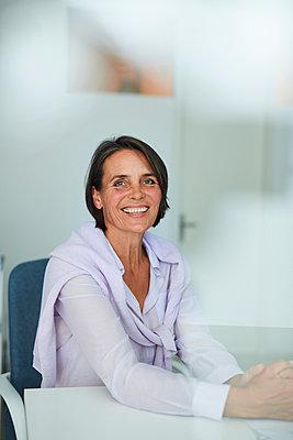 Portrait of mature businesswoman sitting at desk in an office - p300m2030106 von Philipp Nemenz
