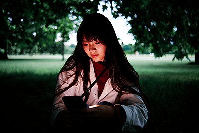 Beautiful young woman using smart phone in public park - p300m2293269 by Angel Santana Garcia