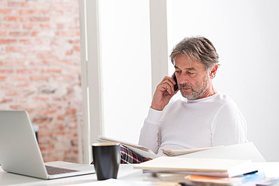 Businessman in pajamas on cell phone at desk - p300m998977f by Westend61
