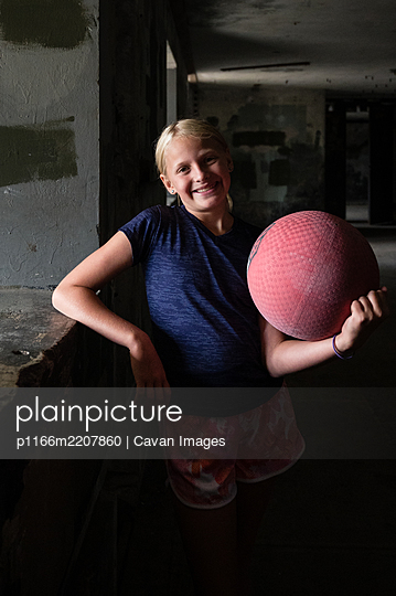 Blond girl holding a red kickball in a dark room - p1166m2207860 by Cavan Images