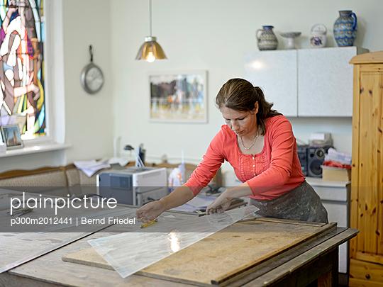 Woman working on glass pane in glazier's workshop - p300m2012441 von Bernd Friedel