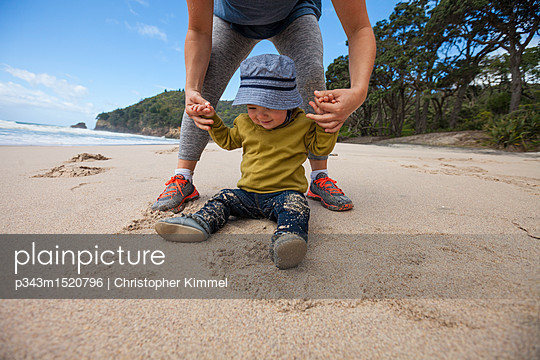 Mother playing with young boy sitting at Waihi Beach in Orokawa Scenic Reserve, New Zealand - p343m1520796 by Christopher Kimmel