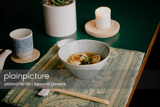 High angle close up of bowl of soup with dumplings in a Ramen and Gyoza restaurant in Italy. - p924m2196783 by Senserini Lucrezia