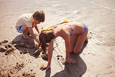 Brother and sister in bathing suit playing in wet sand on sunny summer beach - p1023m1406977 by Sam Edwards