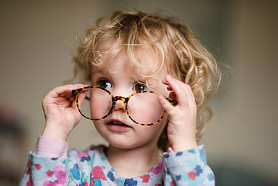 Close-up of girl with eyeglasses at home - p1166m1230395 by Cavan Images