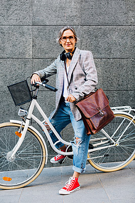 Portrait of confident woman with bicycle against wall on footpath - p1166m1485572 by Cavan Images