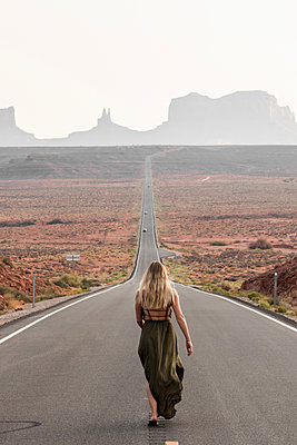 Rear view of female hiker walking on road against clear sky in Monument Valley Tribal Park - p1166m2025117 by Cavan Images