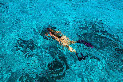 Girl snorkeling in clear blue water - p1166m2189712 by Cavan Images