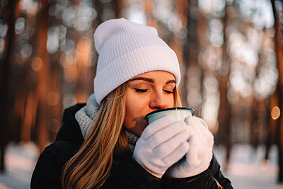 Woman holding cup enjoying hot drink outdoors during winter - p1166m2268818 by Cavan Images