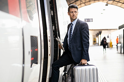 Businessman with suitcase getting in train - p300m2102926 von Daniel Ingold