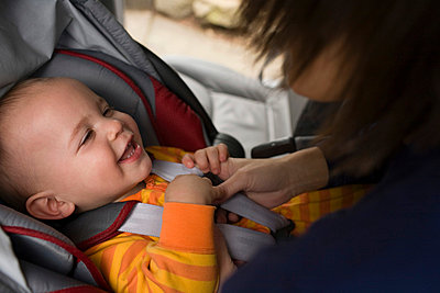 Mother putting baby in car seat - p9248590f by Image Source