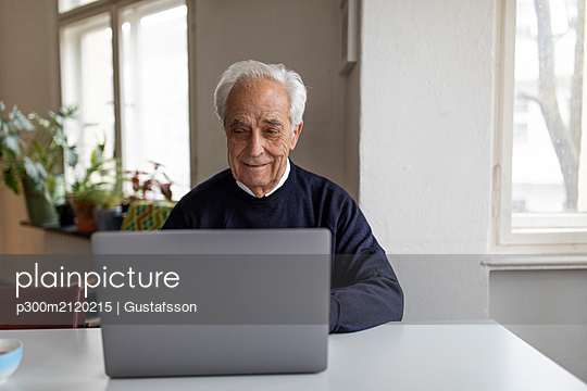 Senior man using laptop on table at home - p300m2120215 von Gustafsson