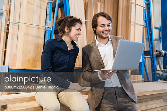 Smiling businessman using laptop while standing by colleague at industry - p300m2250842 by Daniel Ingold