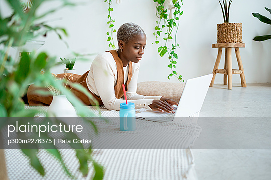 Female professional working on laptop while lying at home - p300m2276375 by Rafa Cortés