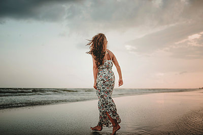 Rear view of woman walking at beach against sky during sunset - p1166m2011183 by Cavan Images