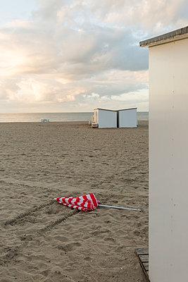 Verlorener Sonnenschirm und Strandhütten - p1271m1548328 von Maurice Kohl