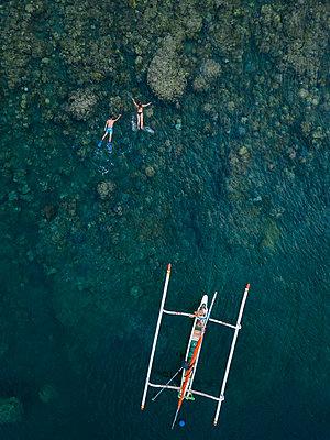 Couple snorkeling in ocean, next to banca boat - p300m2080988 by Konstantin Trubavin
