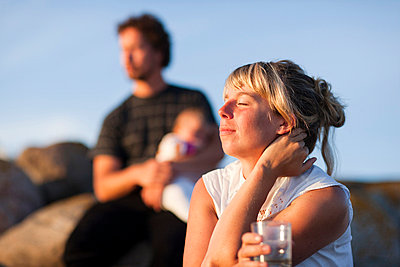 Family relaxing in evening sun - p312m695644 by Peter Rutherhagen
