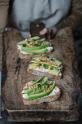 Woman holding chopping board, with ricotta, avocado and walnut bruschetta on top, close-up - p429m1477709 by Alberto Bogo