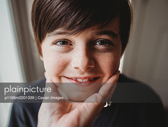 Close up of happy boy's face being held under his chin by a hand. - p1166m2201339 by Cavan Images